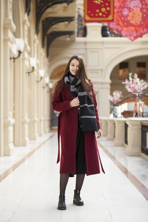 Full body portrait. Young beautiful woman in stylish in a long burgundy coat, indoor shop