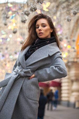Portrait of a young brunette woman in a gray coat with a fur collar on a red square in the center of Moscow
