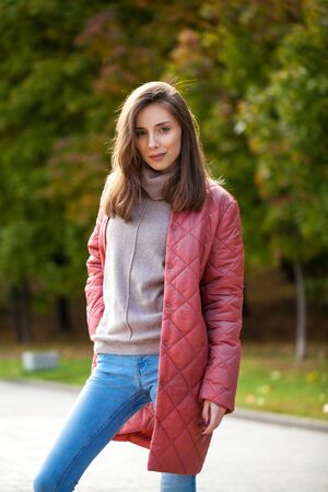 Young stylish brunette woman in light salmon down jacket posing on a background of autumn park