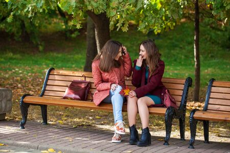 Two beautiful young women resting on a bench in the autumn park