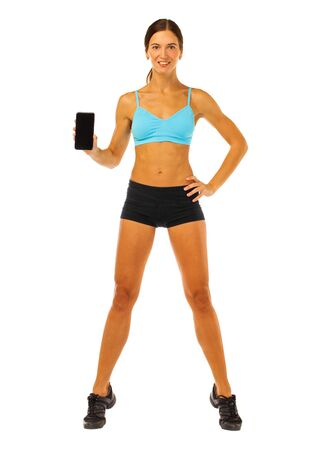 Attractive cheerful young fitness woman showing blank smartphone screen isolated over white background Stock fotó
