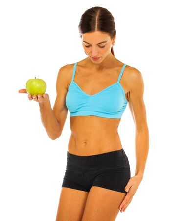 Young athletic girl holding a green apple in her hand - isolated on white background