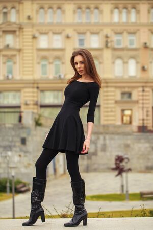 Full-length portrait of young beautiful brunette woman in black dress posing in autumn park on a background of Red Square in Moscow