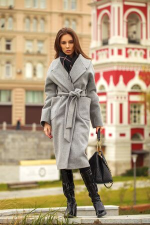 Full-length portrait of young beautiful woman in gray coat posing in autumn park in Moscow