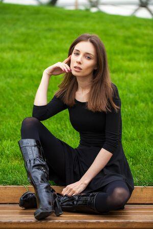 Junge schöne brünette Frau im schwarzen Kleid sitzt auf einer Bank im Herbstpark Standard-Bild