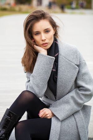 Portrait of a young beautiful brunette woman in gray coat sitting on the stone steps in the autumn park Stock Photo