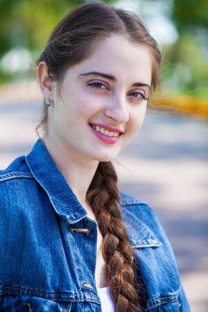 Junges schönes Mädchen in einer Jeansjacke sitzt auf einer Bank in einem Sommerpark