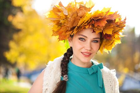 Close up portrait of a young beautiful woman with a wreath of maple leaves posing in autumn park