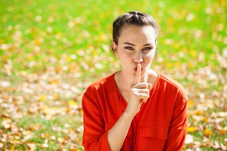 Young beautiful brunette woman has put forefinger to lips as sign of silence, against green summer garden Banco de Imagens
