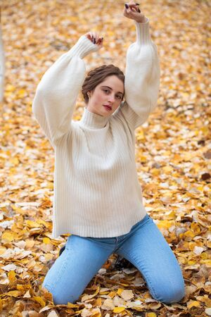 Portrait of a young beautiful girl in blue jeans and gwhite sweater sits on autumn leaves in a park Фото со стока