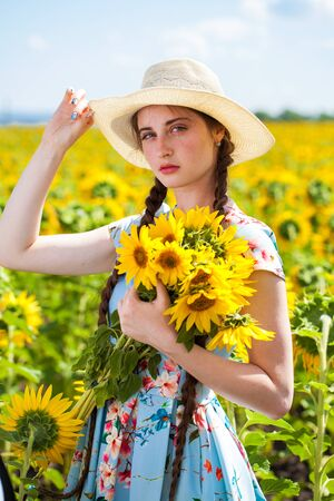 Close up portrait of a young beautiful girl in a field of sunflowers Standard-Bild