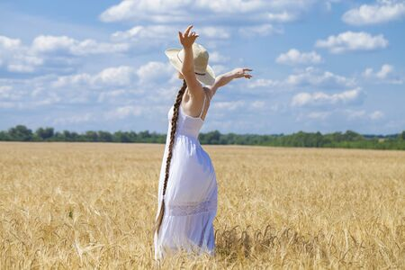 full body, young model in white dress posing against the blue sky in a wheat field