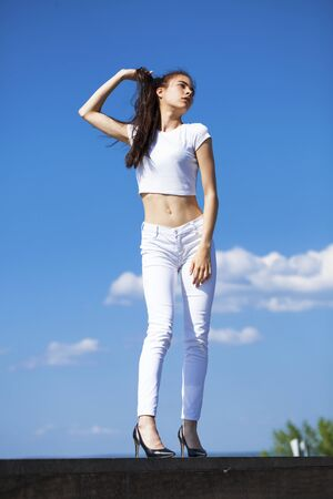 Full body - Young beautiful brunette woman posing against blue sky bright sunny weather