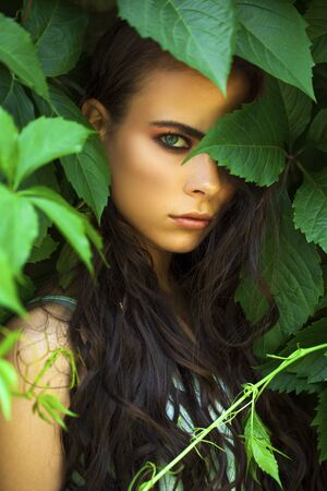 Close up portrait of a young beautiful girl in green ivy foliage Banque d'images