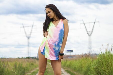 Portrait of a young beautiful woman in colored tunic posing against the background of a meadow field