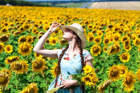Portrait of a young beautiful girl in a straw hat in a field of sunflowers