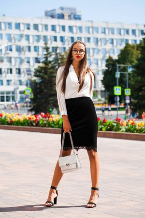 Full-length portrait of a young beautiful woman in a black skirt and white blouse posing on a street background Stock Photo