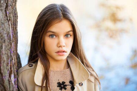 Gelukkig jong meisje in beige jas in herfstpark