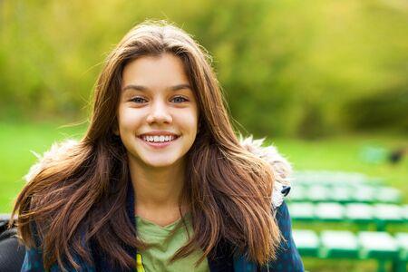 Porträt eines jungen brünetten Mädchens im Hintergrund eines Sommerparks