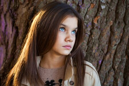 Happy young little girl in beige coat in autumn park