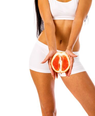 Grapefruit diet. Body part, Young woman in fitness clothing, isolated on white background Reklamní fotografie