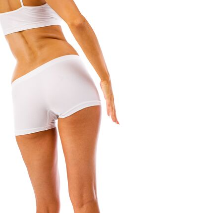 Female thighs and buttocks in white sports shorts, isolated on white background