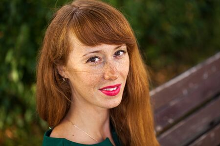 Portrait of a young red-haired woman with freckles. Stock Photo