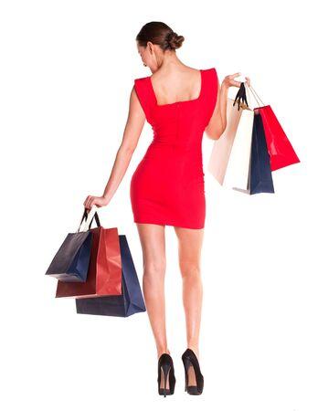 Modefrauenporträt isoliert. Weißer Hintergrund. Glückliches Mädchen halten Einkaufstaschen. Rotes Kleid. weibliches schönes Modell