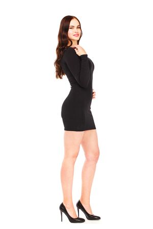 Ritratto in piena crescita di una bella giovane donna bruna in abito nero, isolata su sfondo bianco