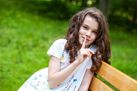 Young beautiful Little girl has put forefinger to lips as sign of silence, outdoors summer 免版税图像