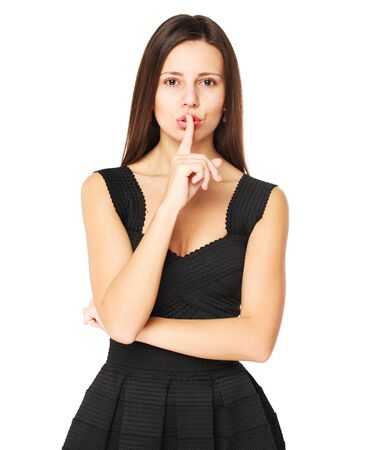 Woman requires silence. Young beautiful brunette girl has put forefinger to lips as sign of silence, isolated on white background
