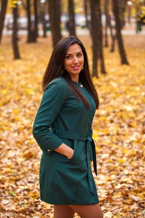 Young brunette woman in green coat on background autumn park