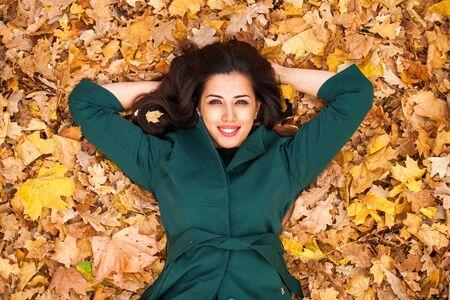 Joven morena en abrigo verde en el parque de otoño de fondo Foto de archivo