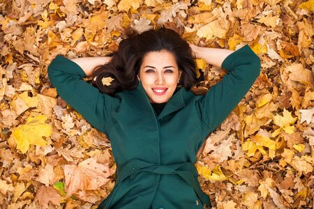 Young brunette woman in green coat on background autumn park Zdjęcie Seryjne