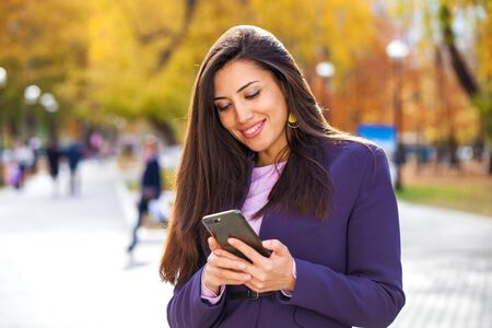 Portrait of a young beautiful brunette calling by smart phone on a background of autumn street