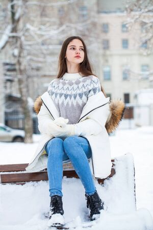 Full body portrait of a young beautiful girl in a white down jacket posing in a winter street Stock Photo