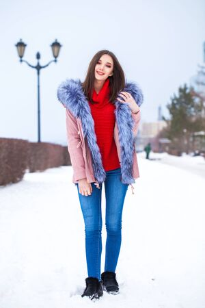 Full body portrait of a young beautiful girl in pink down jacket walking in a winter street