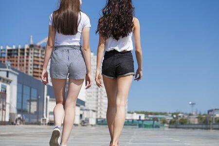 Happy Two girlfriends walking on summer street, outdoors Standard-Bild - 137743023