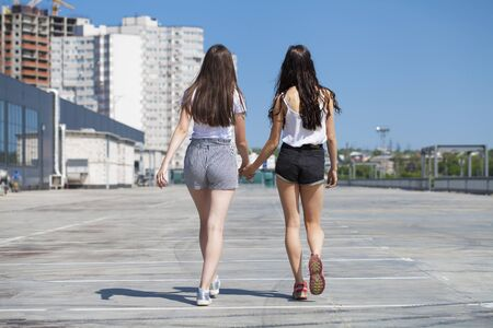 Happy Two girlfriends walking on summer street, outdoors Standard-Bild - 137743034