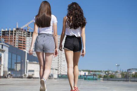 Happy Two girlfriends walking on summer street, outdoors Standard-Bild - 137750027