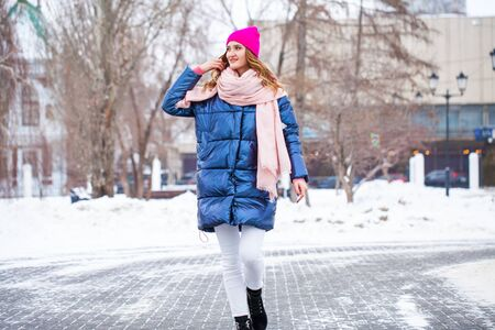Happy young blonde woman in blue down jacket in winter street