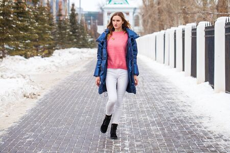 Full-length portrait of a young beautiful woman in a blue down jacket posing in the winter outdoors Stock Photo