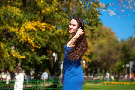 Close up Portrait young beautiful brunette woman in a blue dress walking on the street, autumn park outdoors