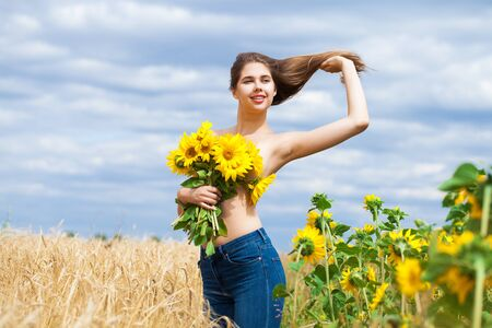 Portrait of a half-naked girl with a bouquet of sunflowers posing on a field background