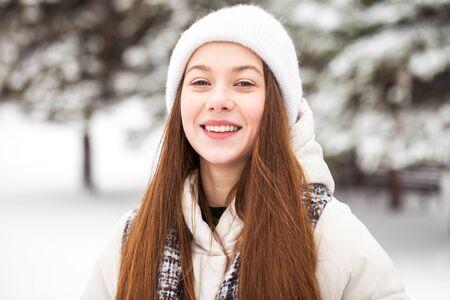 Bliska portret młodej pięknej dziewczyny w białej puchowej kurtce pozowanie w winter park Zdjęcie Seryjne