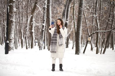 Full body portrait of a young beautiful girl in long white down jacket walking in a winter park