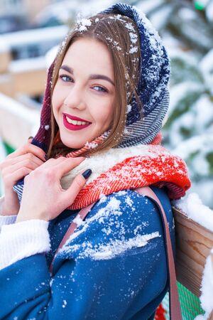 Happy young woman in blue coat posing in winter street