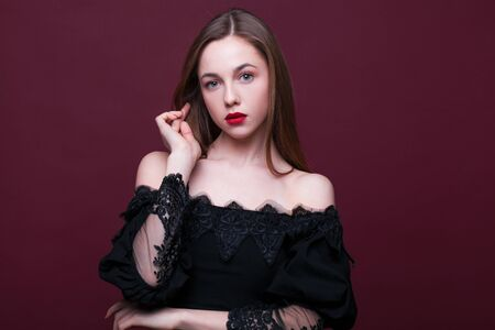 Portrait of a young beautiful girl in black dress posing on a studio crimson background