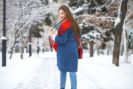 Closeup portrait of a young beautiful girl in winter park