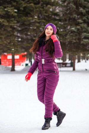 Full-length portrait of a young beautiful brunette girl in a ski suit posing in winter park